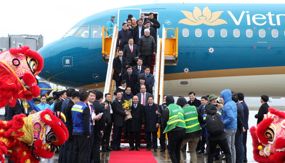 PM Nguyen Xuan Phuc (central) holds a bunch of flowers as he arrived on the first commercial flight, operated by Vietnam Airlines, to land at Van Don International Airport, December 30, 2018. Photo: Tuoi Tre