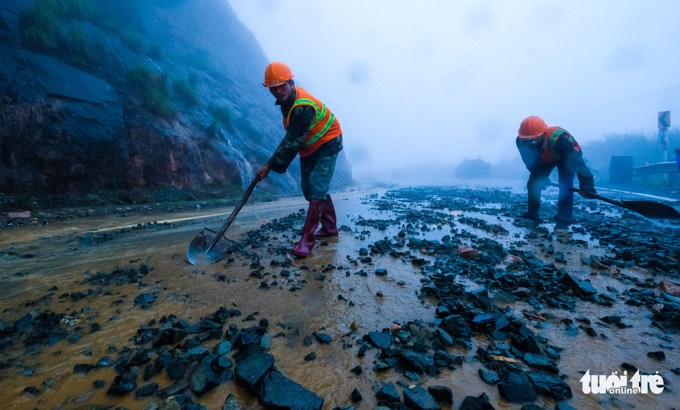 Workers shovel rocks on the mountain pass.  Photo: Tuoi Tre