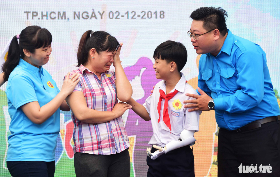 A mother cries after her son, Hoang Hai Dang, a middle school student from Dong Nai Province, had a robotic arm attached to his body thanks to funds raised by Tuoi Tre. Dang suffers bone cancer.