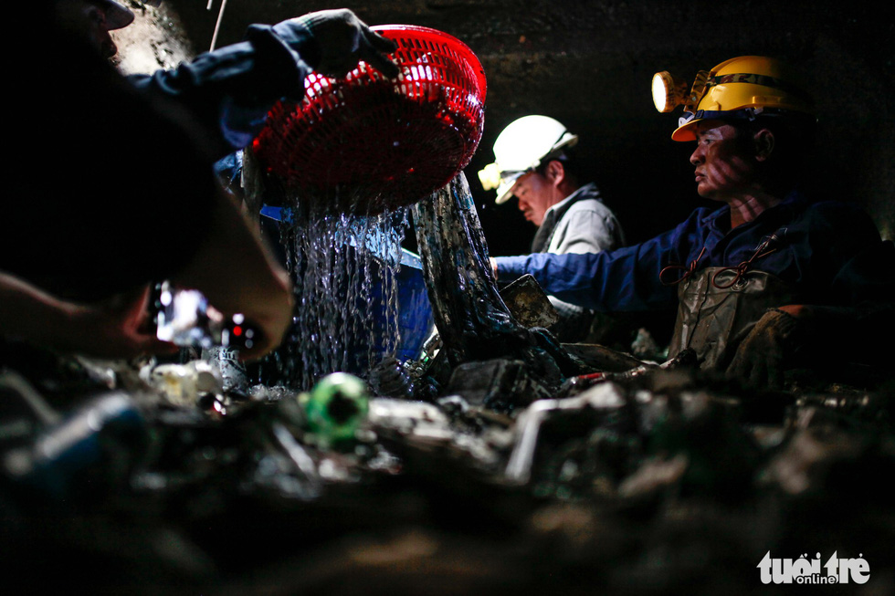 Sanitary workers dredge garbage up from a sewer under Nguyen Thai Hoc Street in District 1, Ho Chi Minh City.