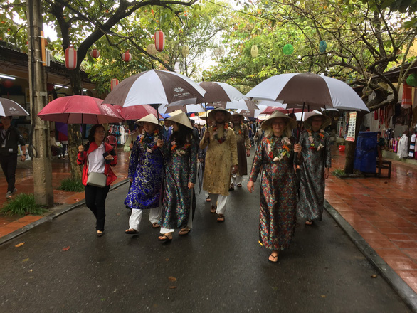 The visitors, in ao dai costumes, tour the UNESCO-recognized Hoi An Ancient Town on January 1, 2019. Photo: Tuoi Tre