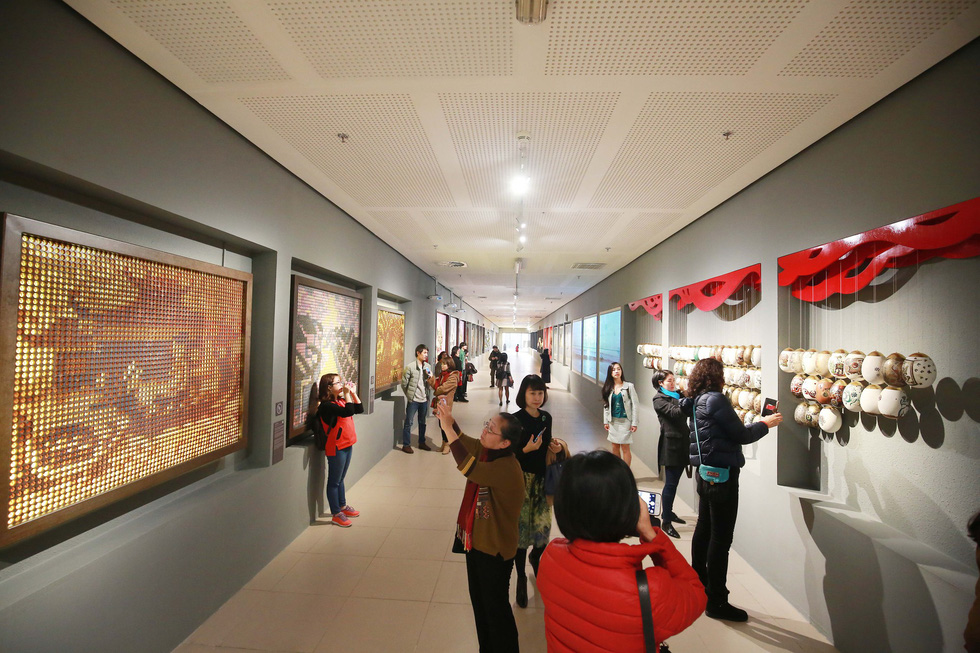 People take pictures of artworks along a corridor of Vietnam's National Assembly building in Hanoi. Photo: Tuoi Tre