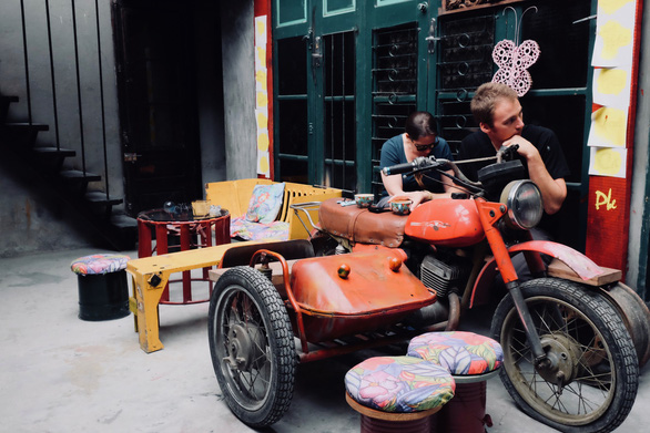 Foreigners sit next to an old-fashion Minks motorbike with a sidecar at Nguyen Van Tho's coffee shop in Hanoi, Vietnam. Photo: Tuoi Tre