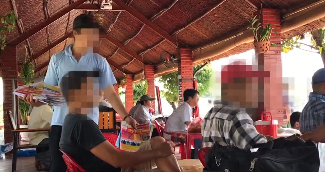 A man hands out leaflets for future competitions at the restaurant. Photo: Tuoi Tre