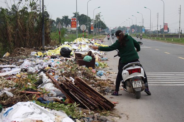 A woman dumps trash on a street in Hanoi. Photo: Tuoi Tre