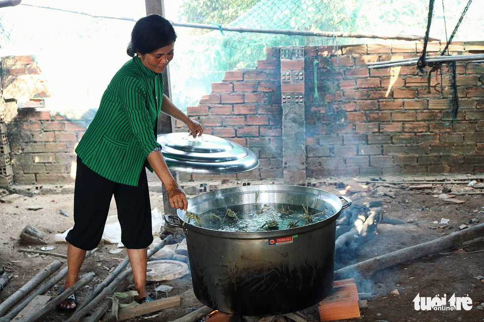 'Banh tet' are cooked in a pot of boiling water over log-fuelled fire. Photo: Tuoi Tre