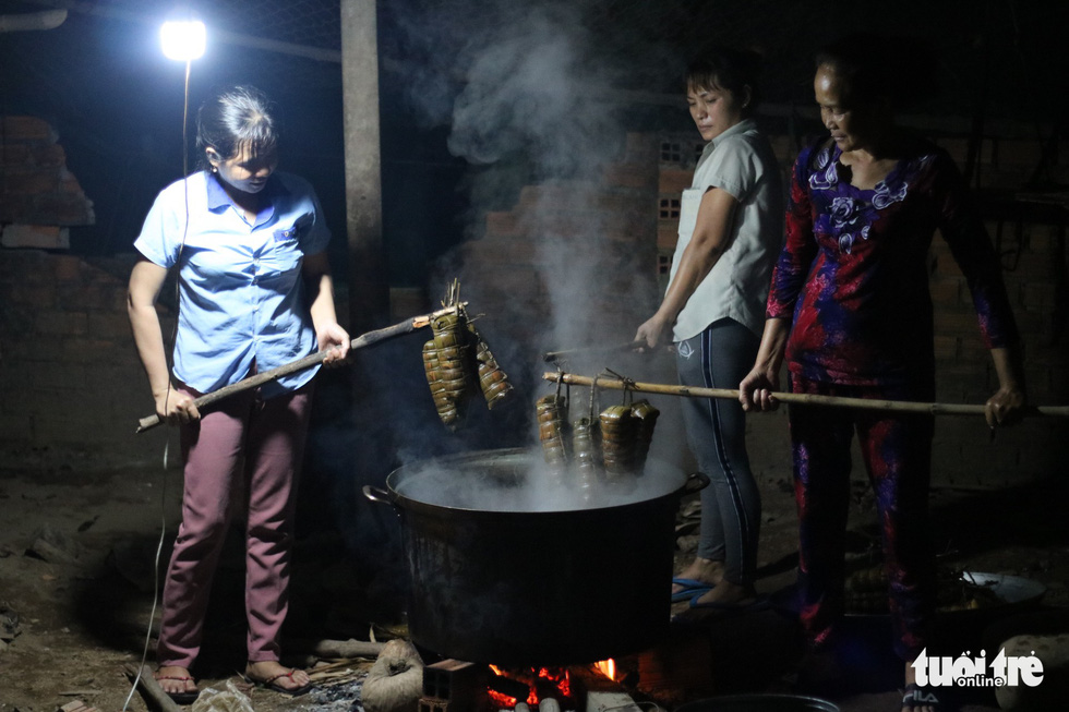 Long sticks are used to remove cooked 'banh tet' from the steaming hot water. Photo: Tuoi Tre