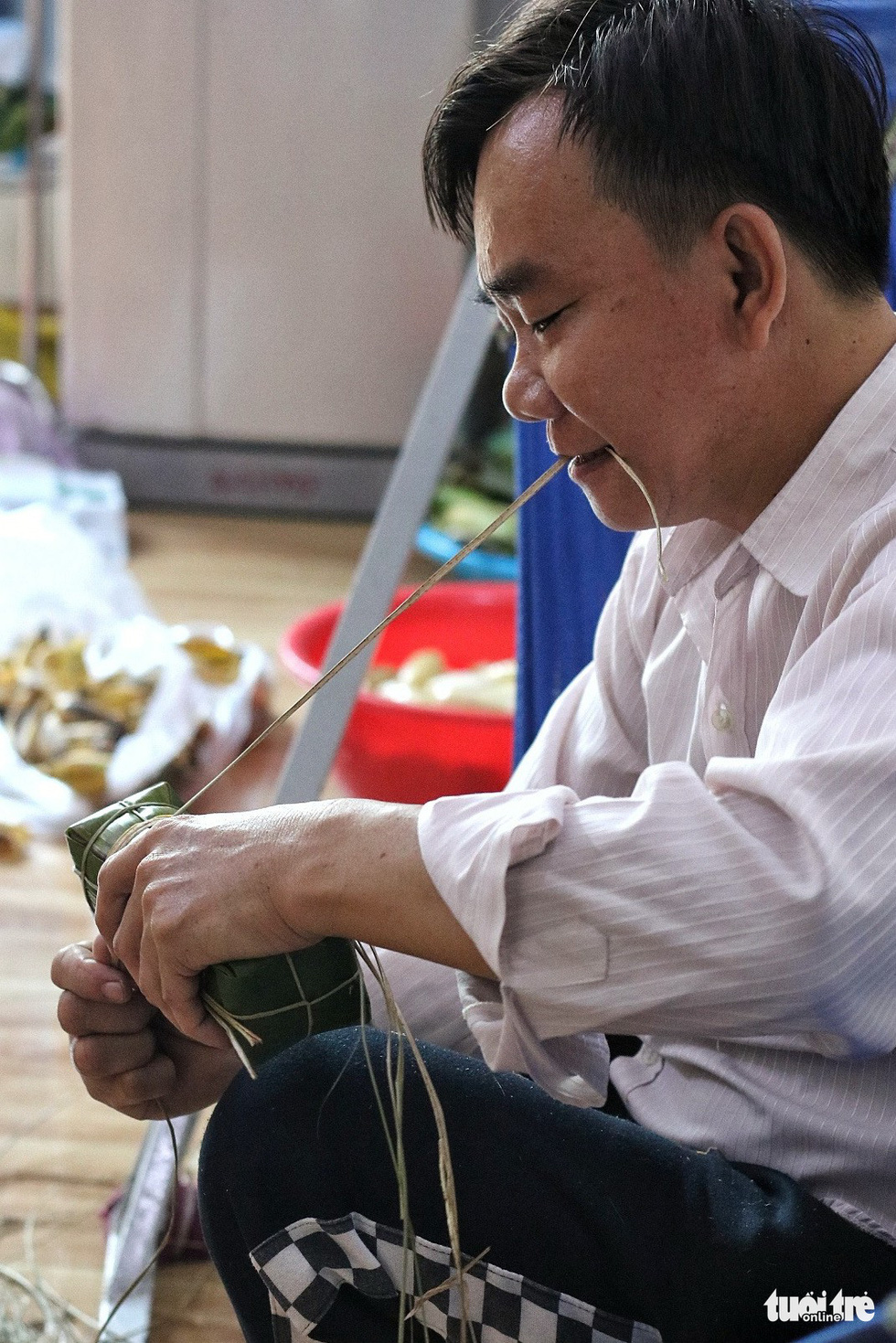 A roll of 'banh tet' is tightened using special strings made from trees in the bamboo family. Photo: Tuoi Tre