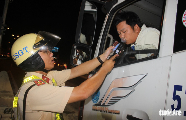 A truck driver is given a breath alcohol test. Photo: Tuoi Tre