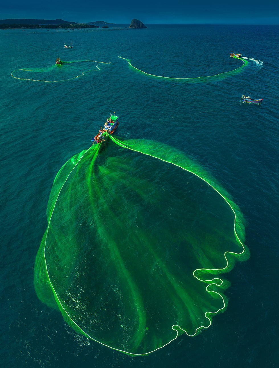 Green nets are sprung across a turquoise sea. Photo: TRAN BAO HOA