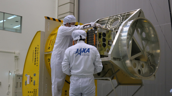Engineers from the Japan Aerospace Exploration Agency (JAXA) fix a satellite to a rocket frame. Photo: JAXA