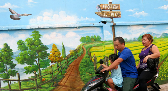 A family is pictured in front of a mural at Ho Thi Ky flower market in Ho Chi Minh City. Photo: Tu Trung / Tuoi Tre
