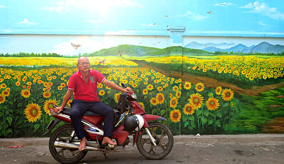 A man is pictured in front of a mural at Ho Thi Ky flower market in Ho Chi Minh City. Photo: Tu Trung / Tuoi Tre