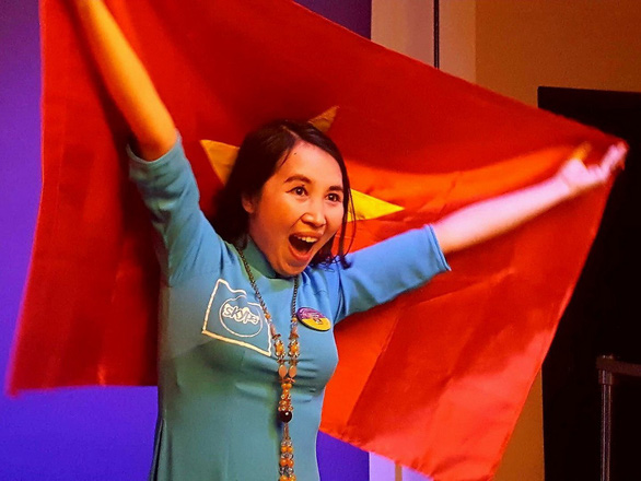 Tran Thi Thuy happily shows off a Vietnamese flag as she is awarded at the Microsoft Education Exchange 2017 conference. Photo: Tuoi Tre