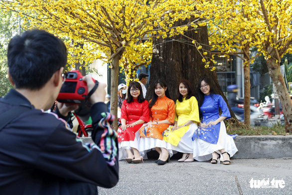 A group of girls don 'ao dai' with modern designs. Photo: Ngoc Phuong / Tuoi Tre