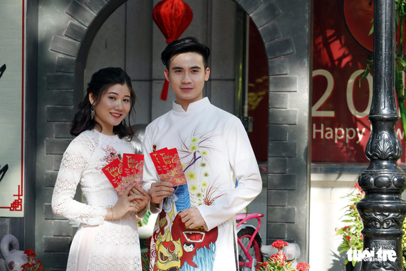 A couple dressed in white 'ad dai' take a photo with red envelops of lucky money. Photo: Ngoc Phuong / Tuoi Tre