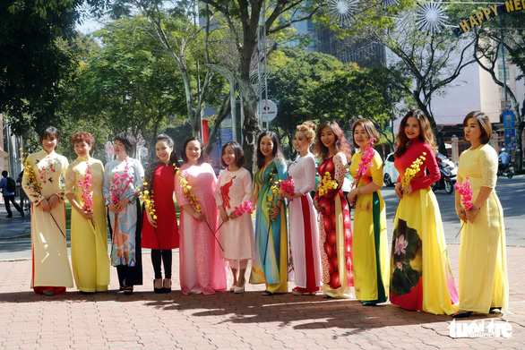 Women take a group photo in front of the Diamond Plaza in District 1. Photo: Ngoc Phuong / Tuoi Tre