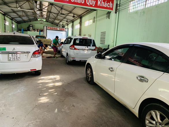 Cars wait for their turn to be repainted at a shop. Photo: Cong Trung / Tuoi Tre