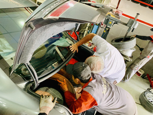 Employee and owner checks a car before maintenance at an establishment. Photo: Cong Trung / Tuoi Tre