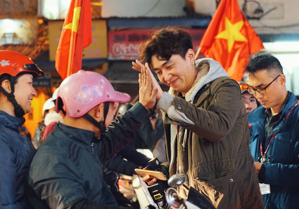 A South Korean reporter gives a high-five to a Vietnamese fan in Hanoi on January 20, 2019. Photo: Nam Tran / Tuoi Tre