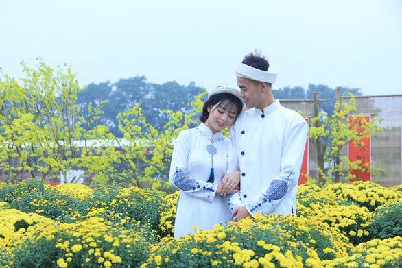 A couple poses for a photo with chrysanthemums in Hanoi. Photo: Duong Lieu / Tuoi Tre