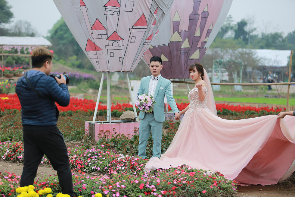 A couple shoots for their pre-wedding photo album at the special garden in Long Bien District, Hanoi. Photo: Tuoi Tre