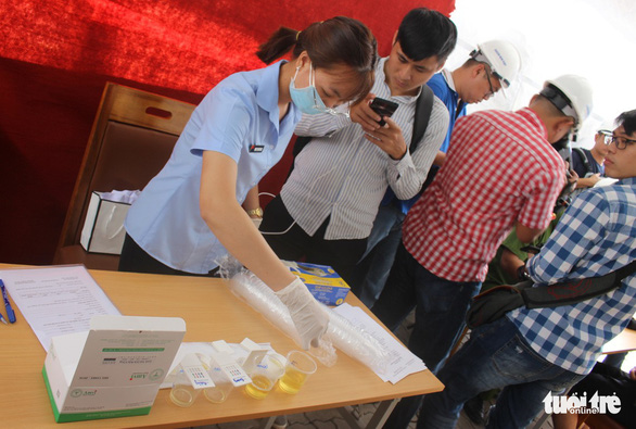 An employee of a local medical center carries out tests at Cat Lai Port. Photo: Son Binh / Tuoi Tre