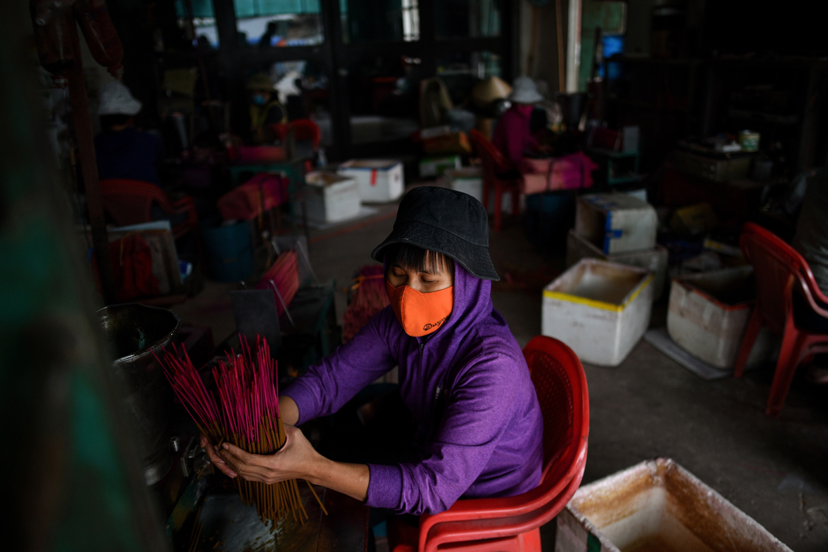 This picture taken on January 4, 2019 shows a Vietnamese worker preparing incense sticks at a workshop in the village of Quang Phu Cau on the outskirts of Hanoi, Vietnam. Photo: AFP