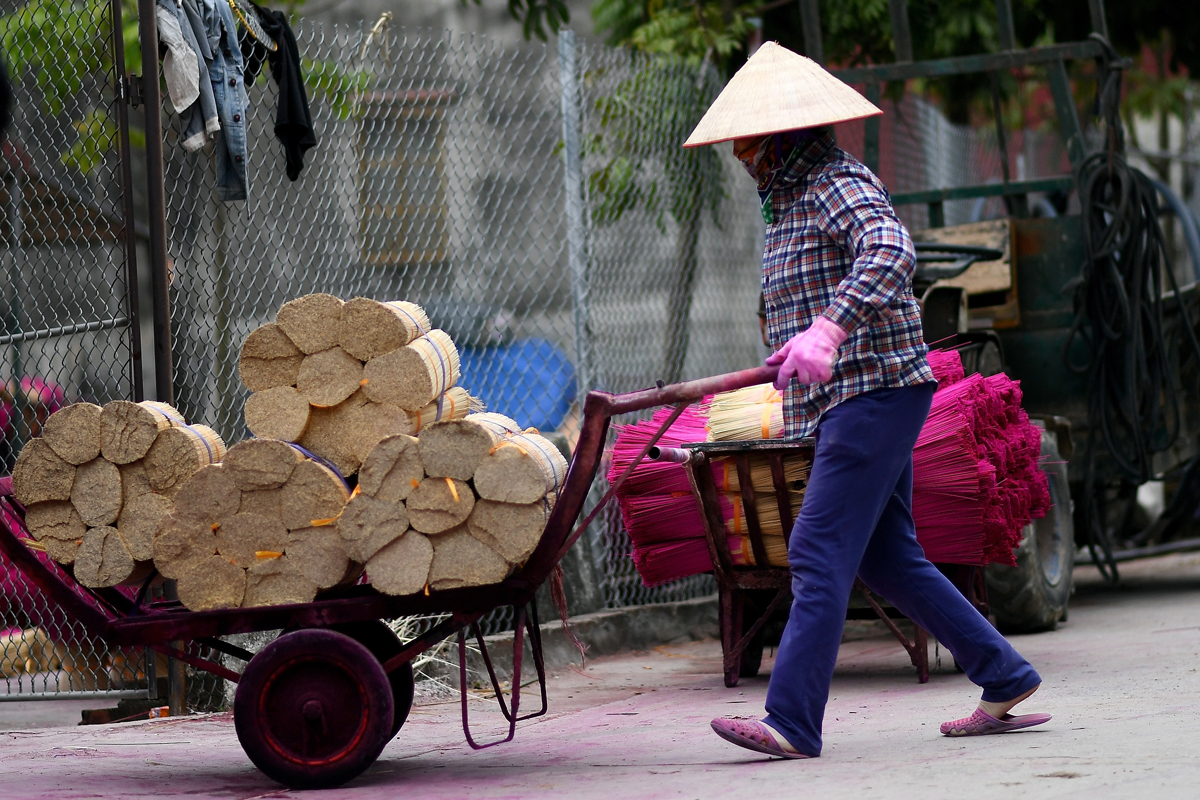This picture taken on January 3, 2019 shows a Vietnamese woman carrying bamboo sticks for dying at a workshop in the village of Quang Phu Cau on the outskirts of Hanoi, Vietnam. Photo: AFP