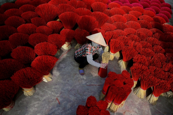 This picture taken on January 3, 2019 shows a Vietnamese woman collecting incense sticks in a courtyard in the village of Quang Phu Cau on the outskirts of Hanoi, Vietnam. Photo: AFP