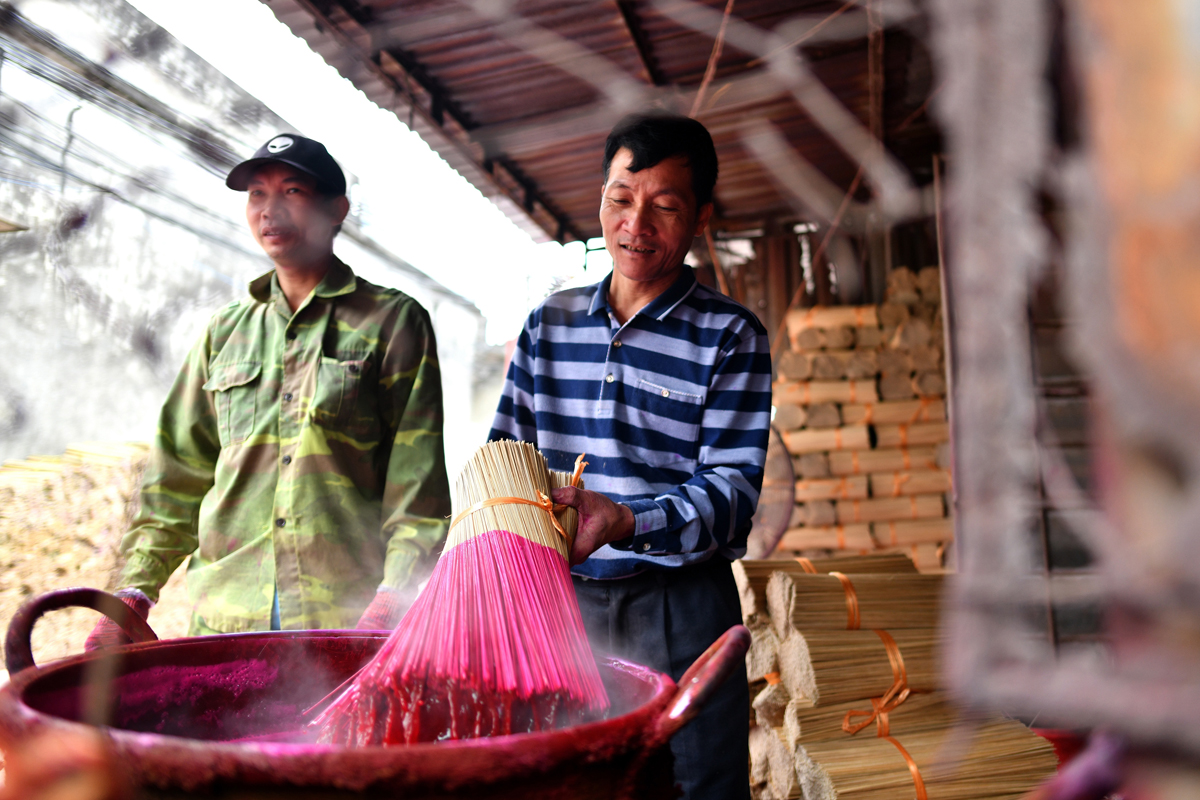This picture taken on January 4, 2019 shows Vietnamese workers dying bamboo incense sticks at a workshop in the village of Quang Phu Cau on the outskirts of Hanoi, Vietnam. Photo: AFP