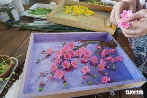 Clay flowers are placed in a wooden frame and can last up to two years. Photo: Tuyet Kieu / Tuoi Tre