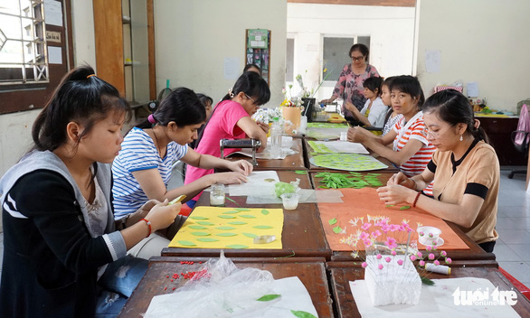 Students of the clay flower class concentrate on their work to finish the pieces before Tet. Photo: Tuyet Kieu / Tuoi Tre