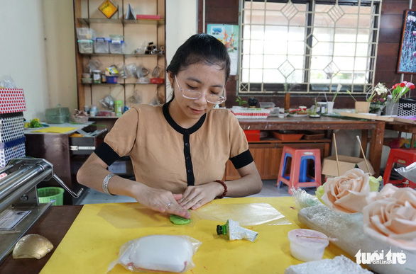 A student of the class mixes the clay with the green color powder to make the leaves. Photo: Tuyet Kieu / Tuoi Tre