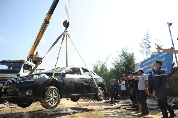 The car is seen above the ground after it is carried from the Hoai River in Hoi An City, central Vietnam, January 25, 2019. Photo: Tuoi Tre