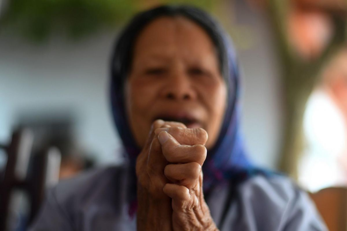 A leprosy survivor offering prayers on the 15th day of the lunar month at a pagoda in the Van Mon Leprosy Hospice compound on Jan 20, 2019. Photo: AFP