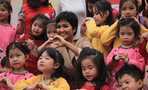 H'Hen Nie takes a photo with children at the event in Hanoi on January 25, 2019. Photo: Nguyen Hien / Tuoi Tre