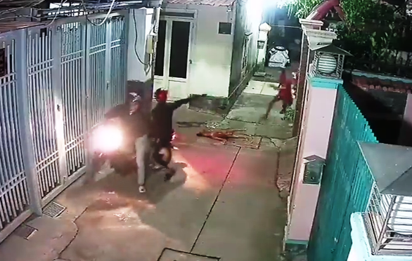 A dog thief threatens a house owner with a harpoon gun in this still photo taken from the surveillance footage of a dog theft in Thu Duc District, Ho Chi Minh City on January 25, 2019.