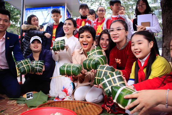 Local students join the banh chung-wrapping event in Hanoi on January 25, 2019. Photo: Nguyen Hien / Tuoi Tre