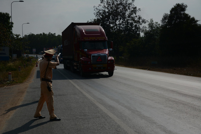 An officer pulls a tractor trailer over at a police checkpoint in Binh Thuan Province, Vietnam. Photo: Duc Trong / Tuoi Tre