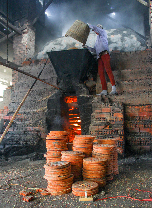 A worker stokes a kiln with rice husks at a stove workshop in Ho Chi Minh City, Vietnam, January 2019. Photo: Thanh Yen / Tuoi Tre