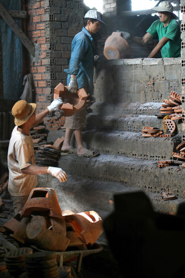 Workers carry ceramic stoves out of a kiln at a workshop in Ho Chi Minh City, Vietnam, January 2019. Photo: Thanh Yen / Tuoi Tre