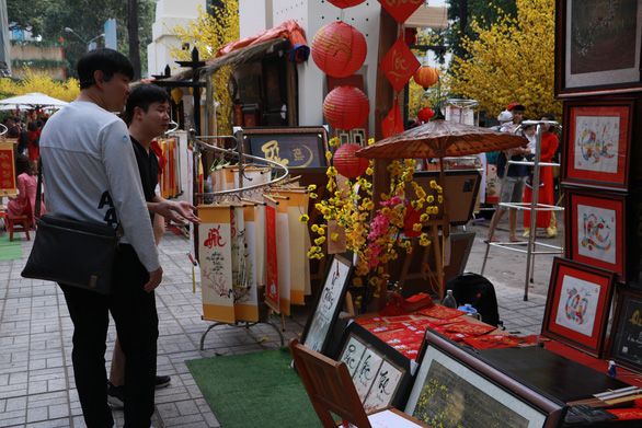 <em>Two South Korean tourists visit a calligraphy booth at </em>Pho Ong Do<em> on January 27,2019. Photo: </em>Binh Minh / Tuoi Tre