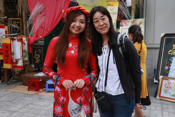 <em>Miyoko (R), a Japanese visitor, poses for a photo with a Vietnamese woman wearing </em>ao dai<em>. Photo: </em>Binh Minh / Tuoi Tre