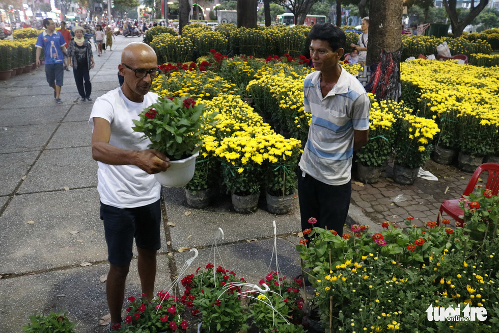 A foreigner lifts a pot of flowers at 23-9 Park in Ho Chi Minh City, January 2019. Photo: Ngoc Phuong / Tuoi Tre