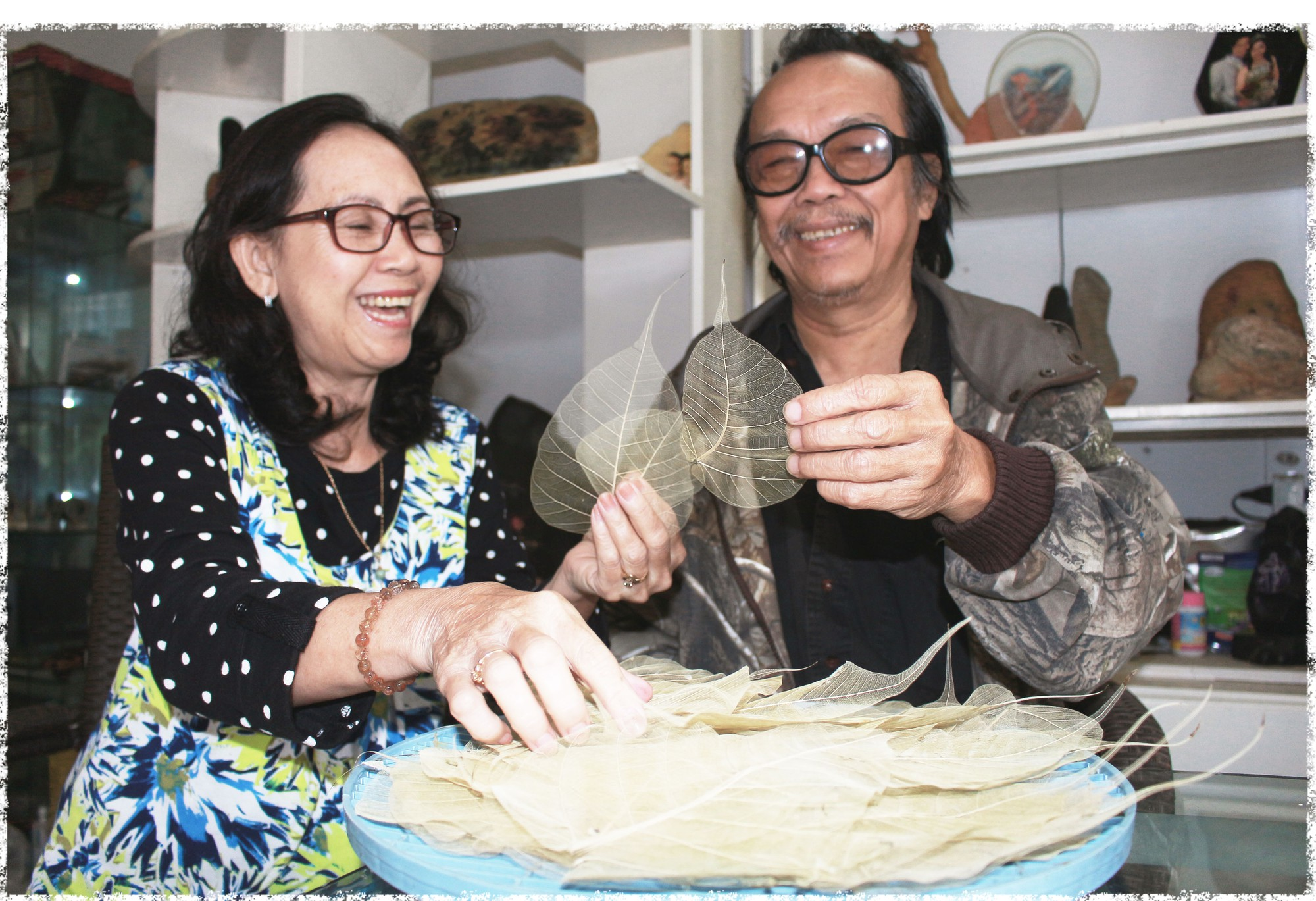 Le Nguyen Vy and his wife hold peepal tree leaves. Photo: Doan Nhan / Tuoi Tre