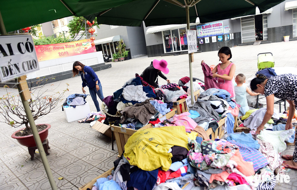 Women choose clothes at the Son Ky 1 Apartment Building Complex in Ho Chi Minh City, Vietnam. The laminated paper sign reads 'Give if you have.' Photo: Duyen Phan / Tuoi Tre