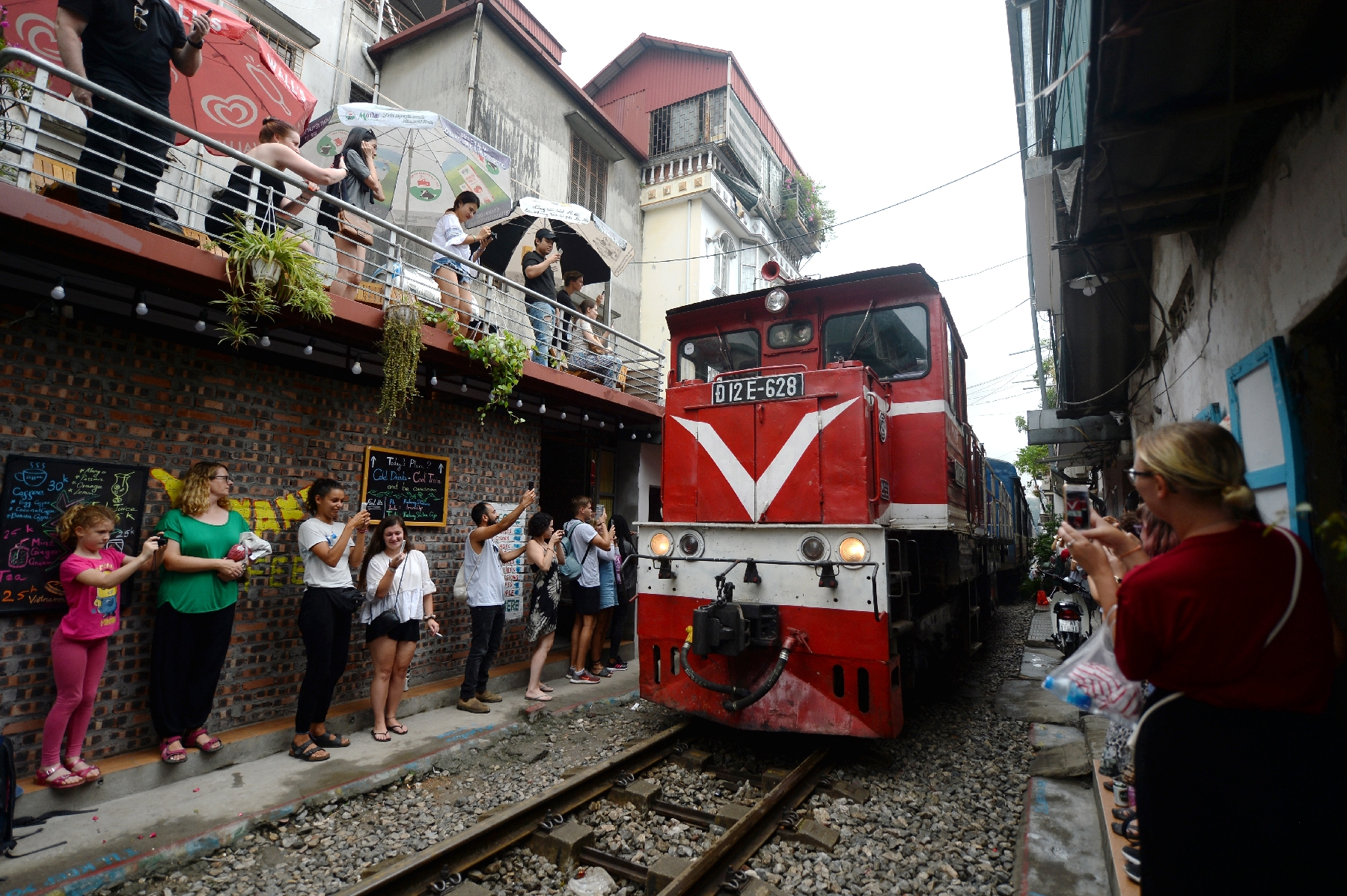 Tourists take pictures when a train goes through the railway in Hanoi's Old Quarter. Photo: AFP
