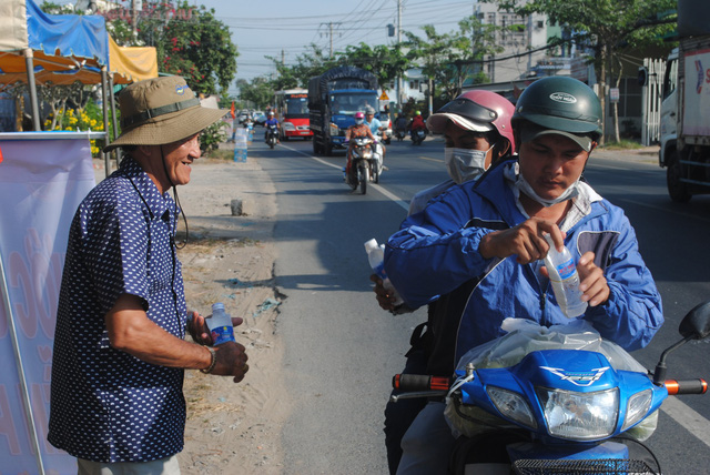 Nguyen Van Thanh talks with a woman who is holding a water bottle he has given along road crossing Dong Thap Province, southern Vietnam, January 30, 2019. Photo: Thanh Nhon / Tuoi Tre