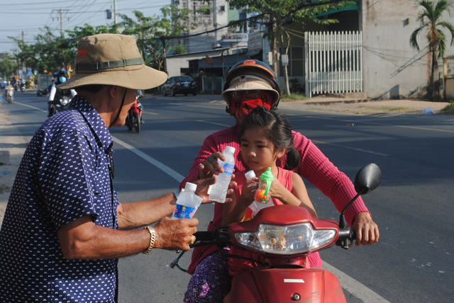 Nguyen Van Thanh gives a bottle of drinking water to a woman on a road in Dong Thap Province, southern Vietnam, January 30, 2019. Photo: Thanh Nhon / Tuoi Tre